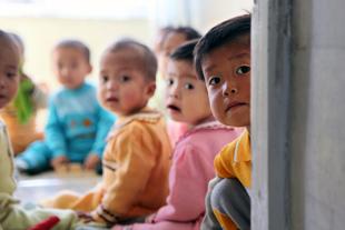 Unos niños sentados en un salón.
